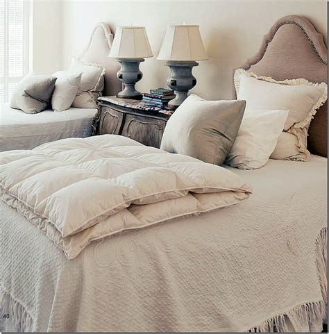 bed with a lot of pillows guest ro0m has two headboards with nailheads lots of