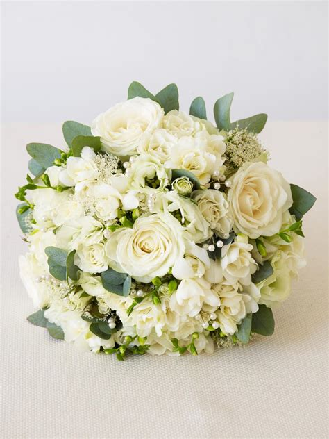 wedding flowers all dressed in white flower arrangements for a winter