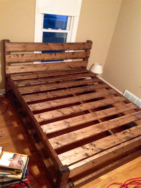 brown wooden bed frame with four legs also