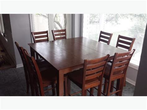 pub style dining room set table with 8 chairs and a lazy