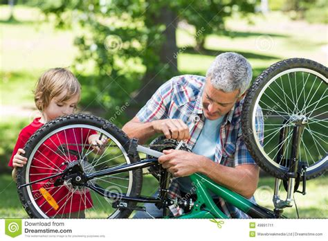 father and his son fixing a bike stock image image 49891711
