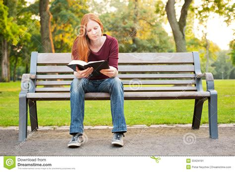 women bench a woman on a bench reading a bible stock image image