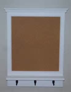 wood framed bulletin board with shelf and three hooks