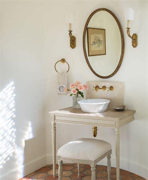 cream and blue french powder room with wood herringbone
