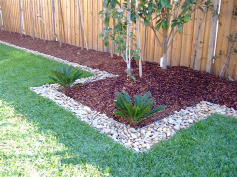 red wood chips  stones   front hedge garden