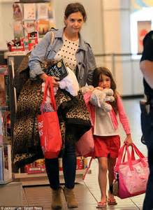 Katie Holmes and Suri lug their own bags as they jet back from Ohio on