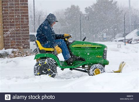 john deere riding lawn mower fitted with a snow plow