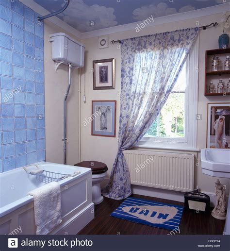 bathroom voile pale blue tiles above bath in bathroom with blue white voile curtain stock photo