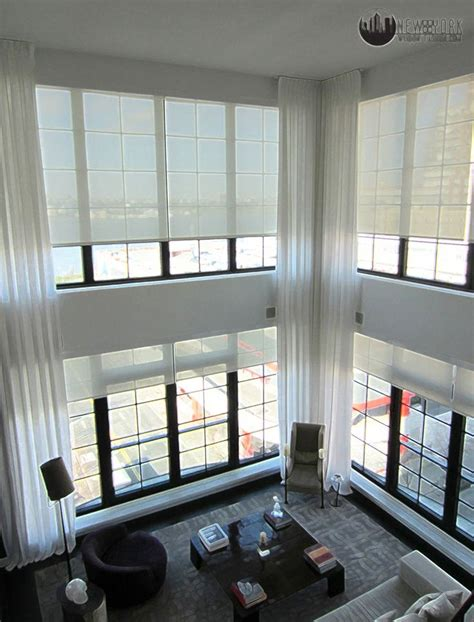 Double height white curtains emphasise the ceiling height