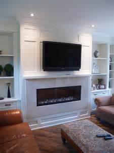 paneled fireplace and built in cabinetry paneled ceiling