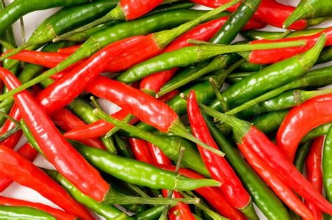 wallpaper of green chillies red and green chili peppers at the background stock