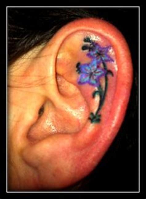 flower tattoo inside ear blue ink flower left ear tattoo want an earring in the