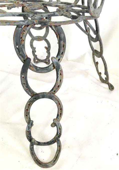 pair of vintage sculptural cast iron horseshoe chairs at