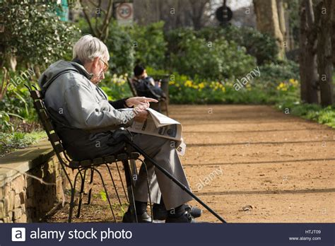 sitting on a park bench an old man sitting on a park bench reading a newspaper in