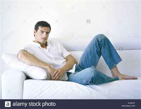 lounging on the couch man lounging on sofa stock photo royalty free image