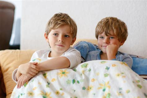 little kid couch two little kid boys watching tv at home stock photo