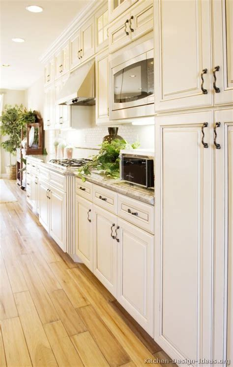 Antique White Kitchen With Wood Floors And An Island Sink White Kitchen Cabinets Wood Floors