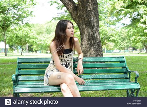 girl sitting on bench asian girl sitting on a bench in a park stock photo