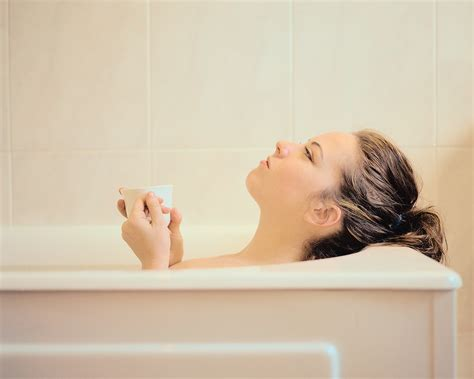 bathroom lady photo woman lying in a bathtub holding a mug successful living