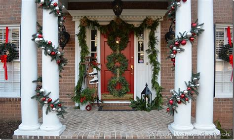 front porch decorated for christmas with three wreaths on