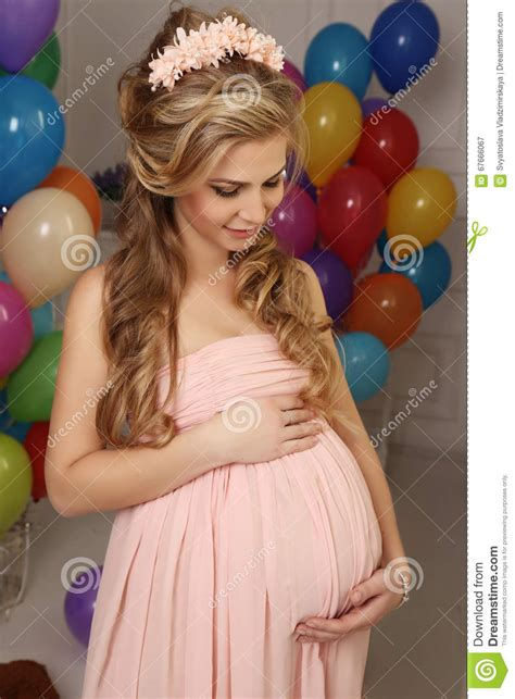 Pregnant Woman With Long Blond Hair In Elegant Dress, With A Lot Of Colorful Air Balloons Stock