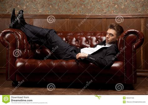 yes man dead on couch a man in a suit lying on the couch royalty free stock