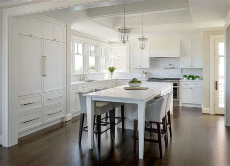 white kitchen island with legs as dining table lined with