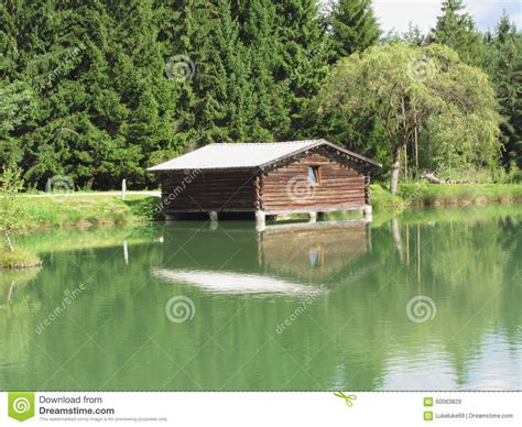 house over water small mountain lake with house over water and forest background fie allo sciliar south tyrol