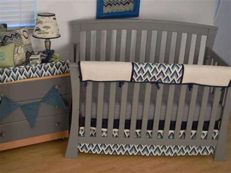 navy grey crib bedding with a teething guard on the crib