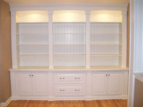 bookshelves custom the trim details at top and bottom lighting is