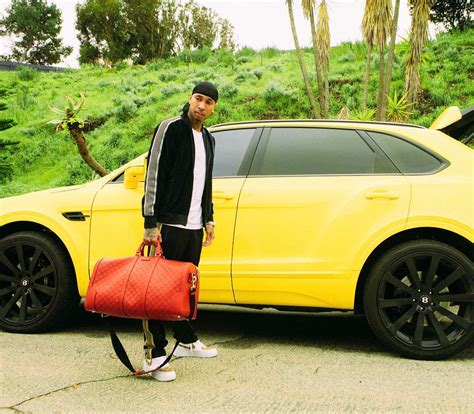 tyga yellow bentley tyga stands by his bentley wearing needles jacket track