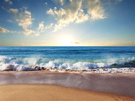 beach sand blue sea waves clouds sun