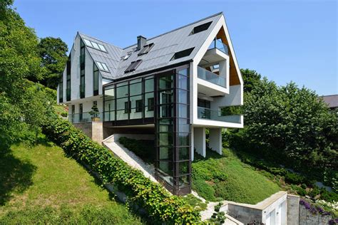 Architectural Home Designs gorgeous glass elevator connects multiple levels on slope
