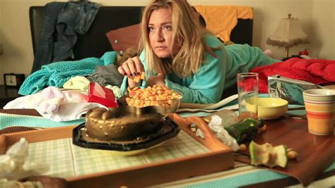 eating in bed portrait of a woman in depression lying on a bed and