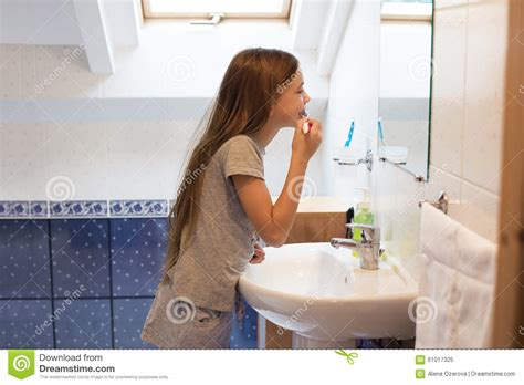 girl in the bathroom girl brushing her teeth stock photo image 61017325