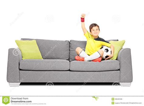 sitting in sofa happy boy with a soccer ball sitting on a sofa and