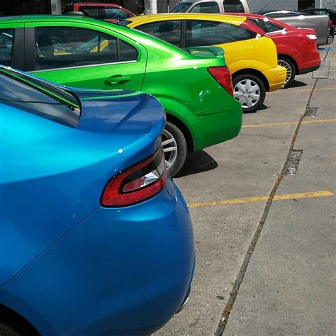 rainbow cars these cars parked in the order of a rainbow
