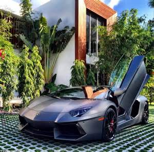 next to an orange mcclaren parked in front of a mansion in malibu