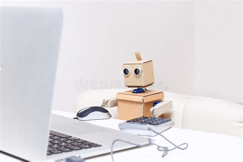 Robot Desk L by Robot Is Sitting At The Table And Working At A Laptop