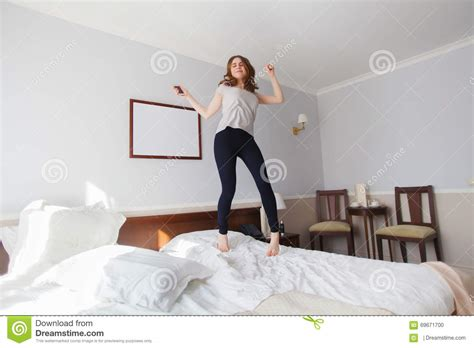 babies jumping on the bed young woman jumps on the bed in bright hotel room stock