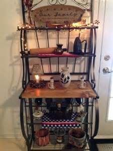 My new bakers rack decorated for the season center shelf has pottery