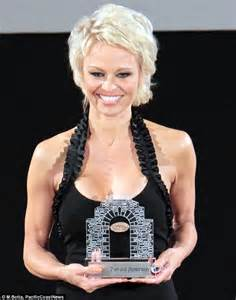 pamela anderson tattoo removal appears surprised by own cleavage
