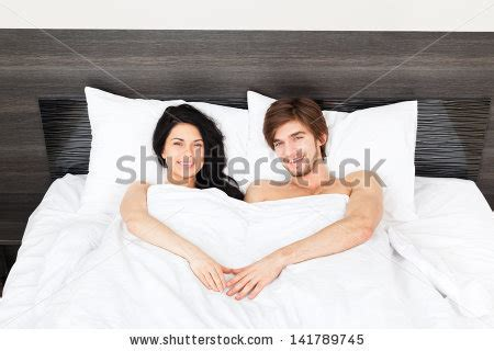 man and woman in the bedroom young couple lying in a bed happy smile man and woman