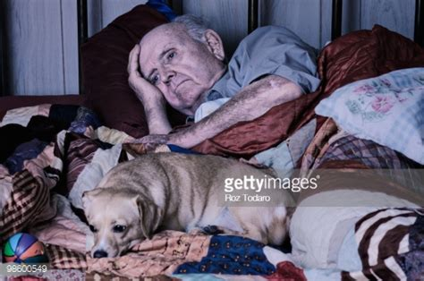 old bed guy depressed old man lying in bed with dog stock photo getty images