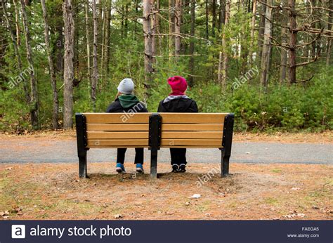 sitting in a park bench two women sitting on a park bench stock photo royalty