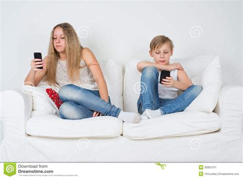 girl sitting on couch boy and girl sitting on the couch with your phone stock