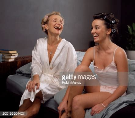 adults in bed hot mother and adult daughter sittting on bed wearing hot rollers stock photo getty images