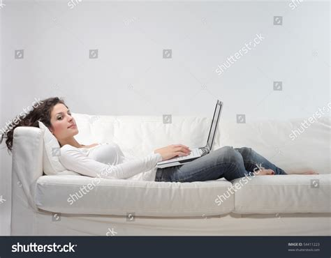 lying on a sofa woman lying on a sofa and using a laptop stock photo