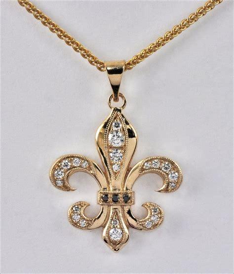 gold fleur de lis and black inscription on shoulder pendants by tom mathis 14k yellow gold fleur de lis