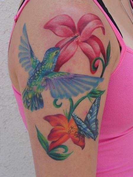 a hummingbird butterfly and flowers make up this